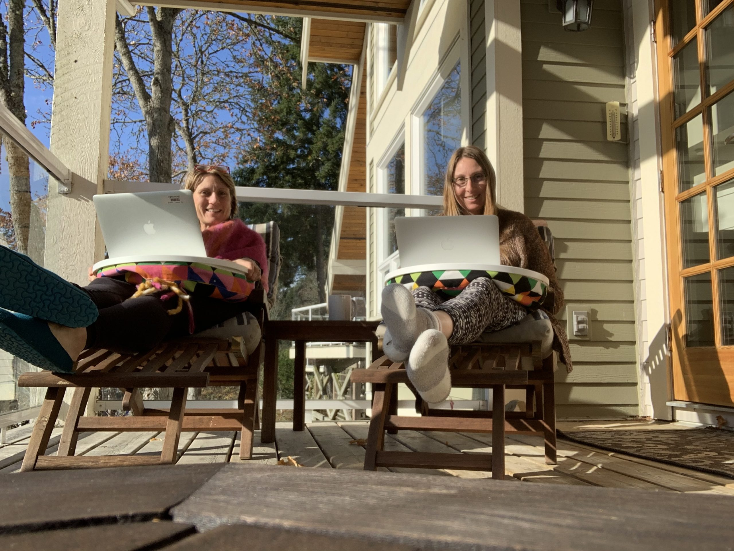 Elspeth and Rowena sitting in lounge chairs on the deck, both typing on laptops